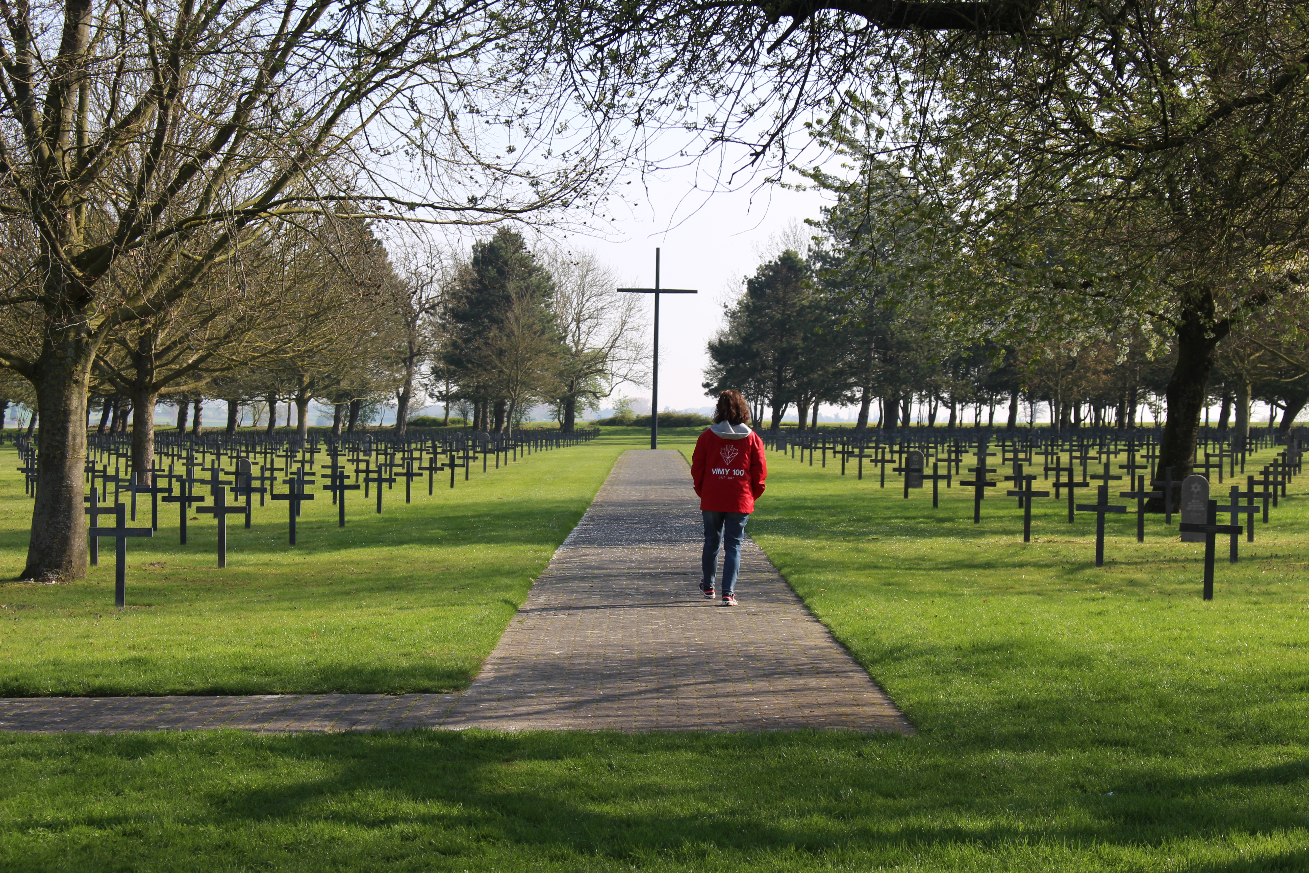 Path with woman walking down it to a tall black cross. Approximately 200 crosses surrounding.