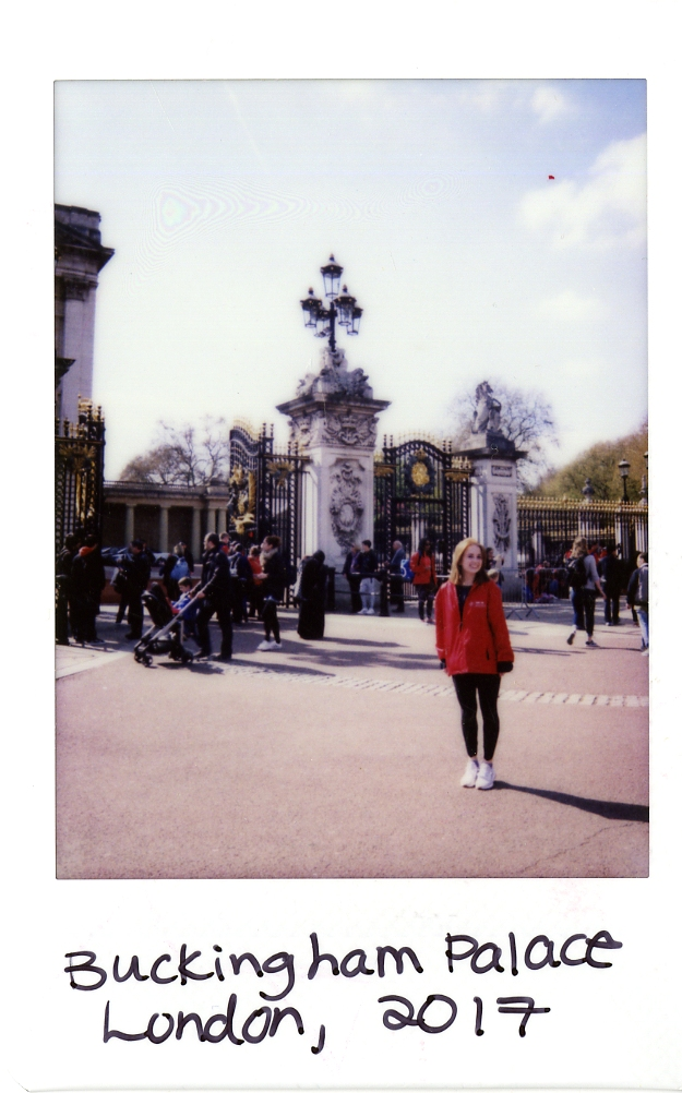Poleroid of Elizabeth standing in front of Buckingham Palace