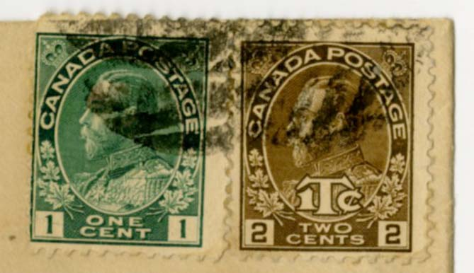Close up of the two stamps from the envelope, one is green and one is light brown. Both have King George V's face on it.